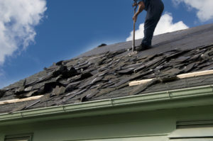 Removing old shingles to prepare a roof for a new installation with blue sky